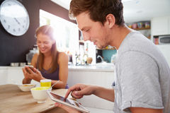 Couple Eating Breakfast Using Digital Tablet And Phone Royalty Free Stock Photo