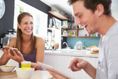 Couple Eating Breakfast Using Digital Tablet And Phone Stock Photography