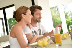 Couple eating breakfast and websurfing on smartphone Royalty Free Stock Photo