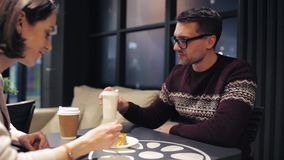 Couple eating cake and drinking coffee at cafe stock footage