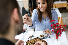 Couple eating can of snails in the restaurant. Royalty Free Stock Photo