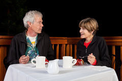 Couple Eating Desert. Older couple having strawberry cake and coffee at an outdoor restaurant Stock Photos