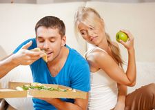 Couple eating different food Royalty Free Stock Photography