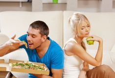 Couple eating different food Stock Images