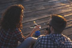 Couple eating dinner while camping at the docks. High angle view of a couple camping at the docks, making and eating dinner and enjoying a sunset stock photography