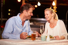 Couple eating dinner at rooftop restuarant Stock Images