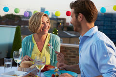 Couple Eating Evening Meal On Rooftop Terrace. Looking At Each Other Smiling stock photo