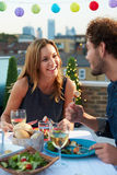 Couple Eating Evening Meal On Rooftop Terrace. Smiling At Each Other royalty free stock images