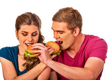 Couple eating fast food. Man and woman eat hamburger. Couple eating fast food. Man and women eat hamburger with ham. Friends holding two burder junk on white Royalty Free Stock Photography
