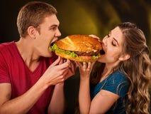 Couple eating fast food. Man and woman treat hamburger . Royalty Free Stock Photos
