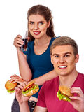 Couple eating fast food. Man and woman treat hamburger . Royalty Free Stock Photos