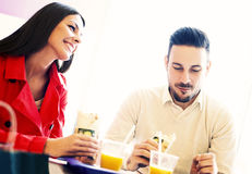 Couple eating in fast food restaurant Royalty Free Stock Image