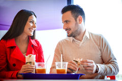 Couple eating in fast food restaurant Royalty Free Stock Photos