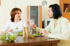 Couple eating fresh vegetables and herbs in a large house Stock Photography
