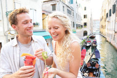 Couple eating fruit snack in Venice. Lifestyle image of beautiful young couple eating healthy on on travel vacation in Venice, Italy. Pretty blonde women and stock photo