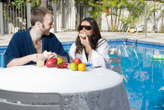 Couple Eating Fruits Near Pool - horizontal Stock Photo