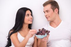 Couple eating grape while having breakfast in bed Royalty Free Stock Image