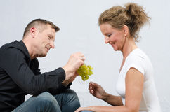 Couple eating grapes - sitting on floor Stock Photography