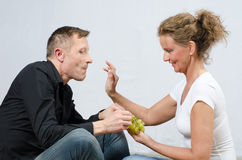 Couple eating grapes - sitting on floor Stock Images
