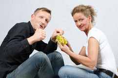 Couple eating grapes - sitting on floor Stock Photos