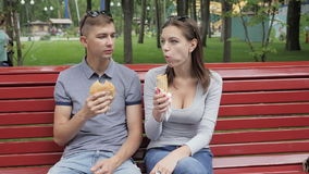 Couple eating a hamburger in a city park stock video