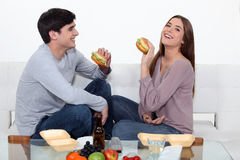 Couple eating hamburgers. At home Stock Images