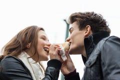 Couple Eating Hotdog Together Against Sky Royalty Free Stock Image