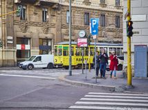 A couple eating Ice cream in front of a tram crossing a street of Zona Magenta neighborhood. Milan, Italy royalty free stock photo