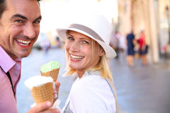 Couple eating ice cream in street on sunny day. Cheerful couple in Rome eating ice cream cones Stock Photography