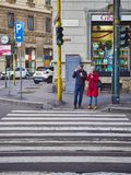 A couple eating ice cream waiting to cross a crosswalk of Zona Magenta neighborhood. Milan, Italy stock photos