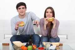 Couple eating junk food Stock Photos