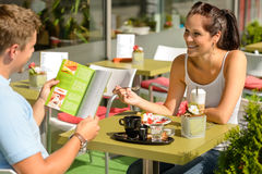 Couple eating looking at menu cafe restaurant. Smiling woman Royalty Free Stock Image