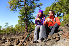 Couple eating lunch taking a break hiking. Enjoying sandwiches. Hikers living active lifestyle in mountain nature. Woman and men hiker sitting on hike on royalty free stock images