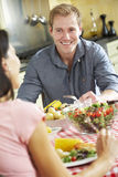 Couple Eating Meal Together In Kitchen Stock Photography