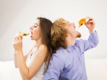Couple eating pizza, having fun together stock images