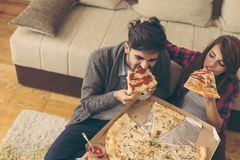 Couple eating pizza for lunch. High angle view of a young couple in love sitting on a living room floor and eating pica. Focus on the guy royalty free stock images