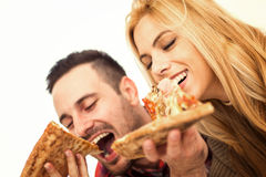 Couple eating pizza. Portrait of an happy couple.They are laughing and eating pizza and having a great time royalty free stock photo