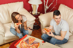 Couple eating pizza and watching TV. Young couple eating pizza and watching TV Stock Photography