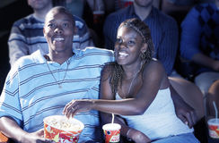 Couple Eating Popcorn While Watching Movie In Theatre. Happy African American couple eating popcorn while watching movie In theatre Stock Photo