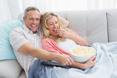 Couple eating popcorn while watching television Stock Photo