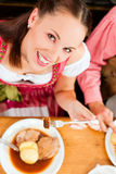 Couple eating roast pork in Bavarian restaurant Royalty Free Stock Photos