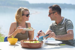 Couple eating salad on terrace near sea stock images
