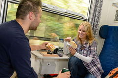 Couple eating sandwiches on train traveling smile. Vacation hungry lunch stock image