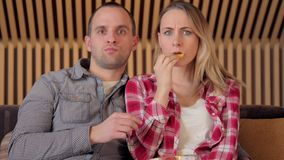 Couple eating snacks and watching scary movie in television, steadycam shot stock video