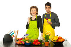 Couple eating strawberries in kitchen. Couple eating strawberries in their kitchen and maaking a break from cooking against white background Stock Image