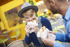 Couple during the eating street food. Adorable couple eating fast food at sidewalk royalty free stock image