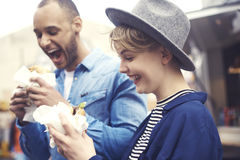 Couple during the eating street food. Cheerful couple having tasty hamburgers royalty free stock photo