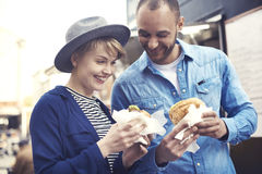 Couple during the eating street food. Happy couple enjoying their meal royalty free stock photography