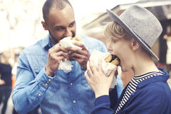 Couple during the eating street food. Couple having delicious burgers outside royalty free stock photography