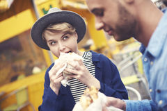 Couple during the eating street food. Young couple having burgers in the sidewalk bar royalty free stock photo